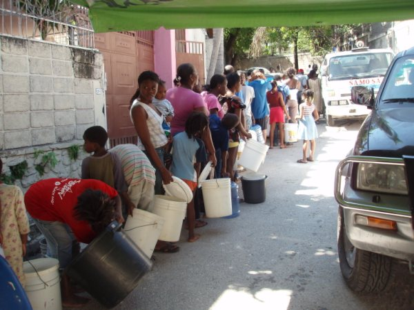 Haitians stand in line to collect water